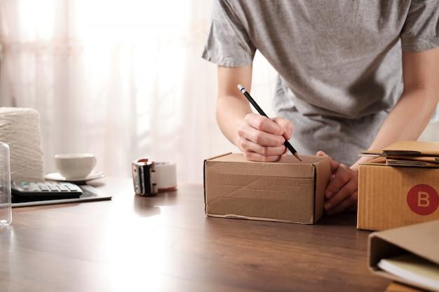 自宅の段ボール箱に住所を書く若いスタートアップビジネス所有者 Premium写真