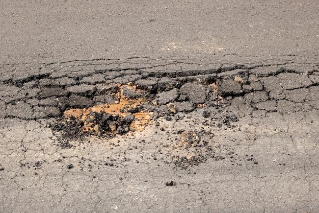 破損したアスファルト壊れた道路輸送大型トラックのポットホール Premium写真