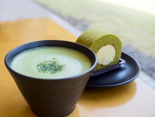 木製のテーブルに熱い抹茶ラテ緑茶と緑茶ロールケーキ Premium写真