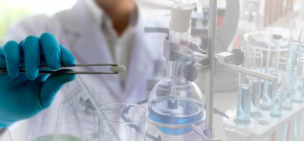薬剤師はトングを使って薬品を実験室で検査します。 Premium写真
