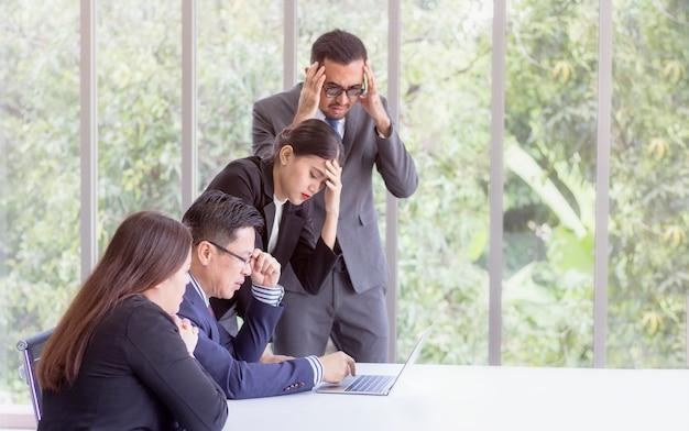 Бизнес-концепция; подчеркнутый босс и исполнительная команда ищут решение проблемы на собрании, партнеры держат головы в руках, унывают от неудач, плохие новости, отчаянно относятся к проблеме компании Premium Фотографии