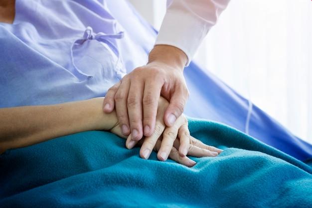Доктор заботится со старой пациенткой в больнице Premium Фотографии
