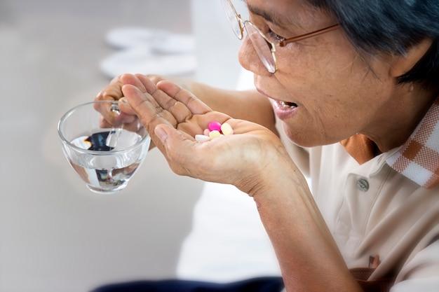 薬と自宅で水のガラスを持つ年配の女性のクローズアップ Premium写真