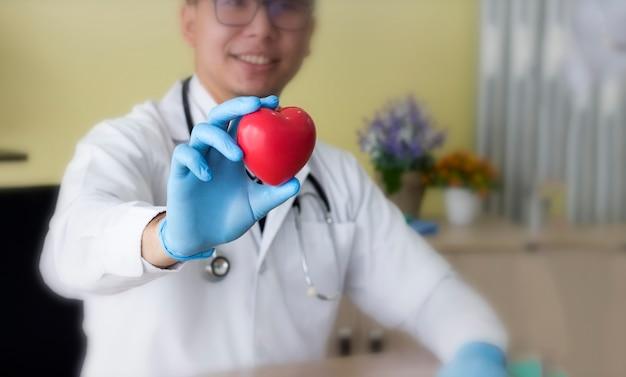 彼の手で心を持って聴診器で医師。 Premium写真