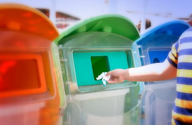 少年は公園のゴミ箱にゴミを入れています。彼はボトルの廃棄物をゴミ箱に入れました。 Premium写真