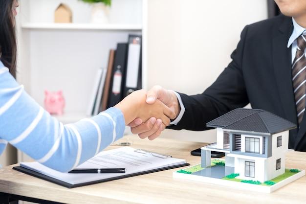 顧客または女性が新しい家のコンセプトを購入するためのローン契約に署名すると言う Premium写真