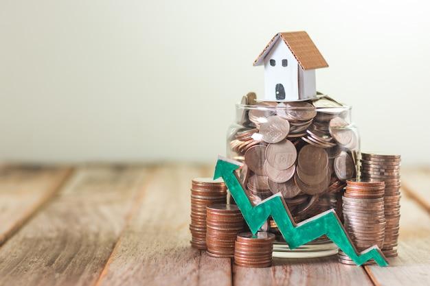 住宅投資、住宅ローン、木製のテーブル背景にガラスの瓶にコインを節約 Premium写真