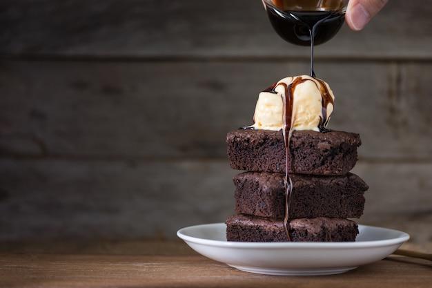 チョコレートブラウニースタックとバニラアイスクリームの上、木製 Premium写真