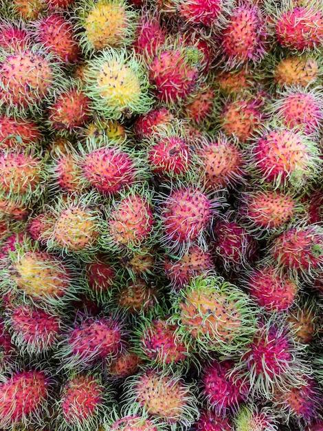 Свежие фрукты рамбутан для продажи на рынке. мягкий фокус. Premium Фотографии