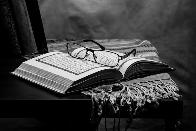 コーラン-テーブルの上のイスラム教徒の神聖な本、静物 Premium写真