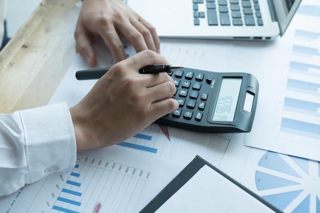 Молодой бизнесмен работая с калькулятором, деловыми документами и компьтер-книжкой Premium Фотографии