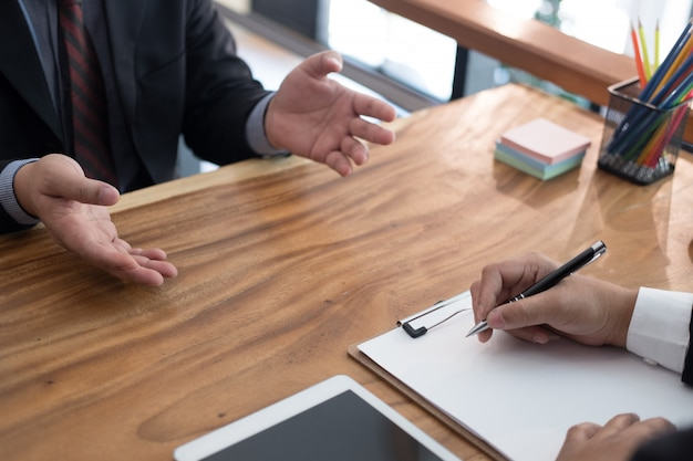 ビジネスの欠員のための就職の面接で候補者に話しているビジネスマン。 Premium写真