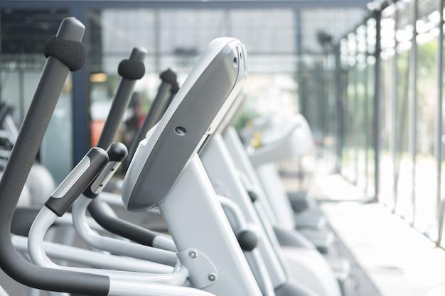 フィットネス施設センター、ジムインテリア、有酸素運動トレーニングとボディービルのためのスポーツトレーニング機器を備えたヘルスクラブ。 Premium写真