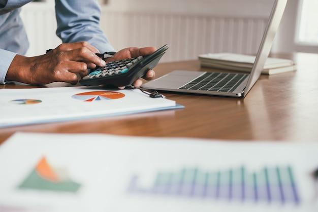財務顧問は、電卓を使用して収益と予算を計算し、会計士は会計を行い、簿記係は計算を行います Premium写真
