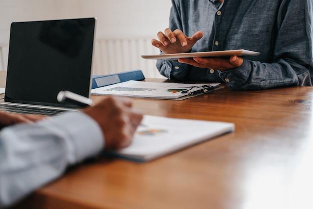 Бизнесмены имеют встречу, бизнесмен работая с командой используя таблетку Premium Фотографии