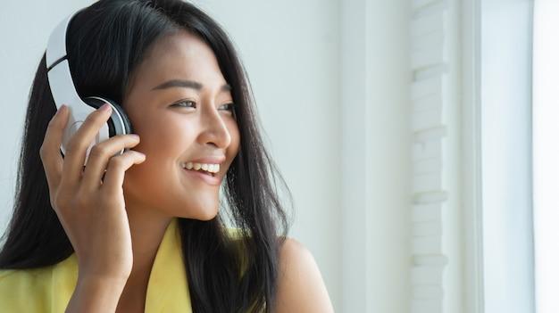 Красивые тайские женщины наслаждаются слушать от беспроводных наушников. Premium Фотографии