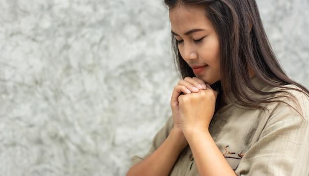 美しいアジアの女の子が神の祝福を祈って立っています。 Premium写真