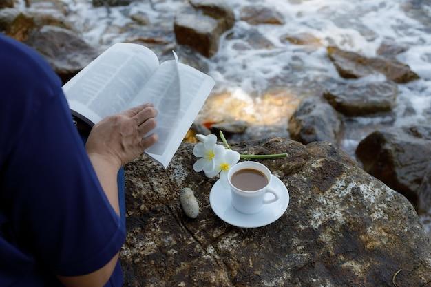 ビーチの休日の読書付きコーヒー Premium写真