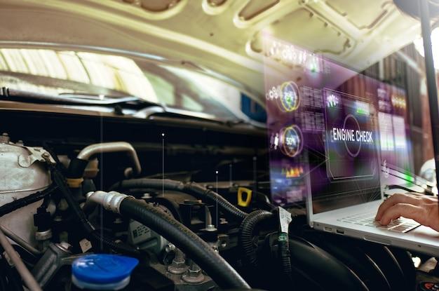 男はホログラムで彼の車のエンジンの分析にラップトップを使用します。エンジンサービスホログラム通信、ネットワーク、保険の概念 Premium写真