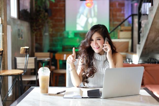 コンピューターで作業してカジュアルな服装でオンライン、若いアジアの女性を販売するビジネス Premium写真