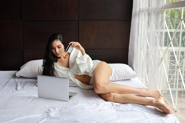 Платье взрослой азиатской сексуальной женщины нося белое ходя по магазинам онлайн на компьютере с кредитной карточкой пока лежащ на кровати в спальне Premium Фотографии