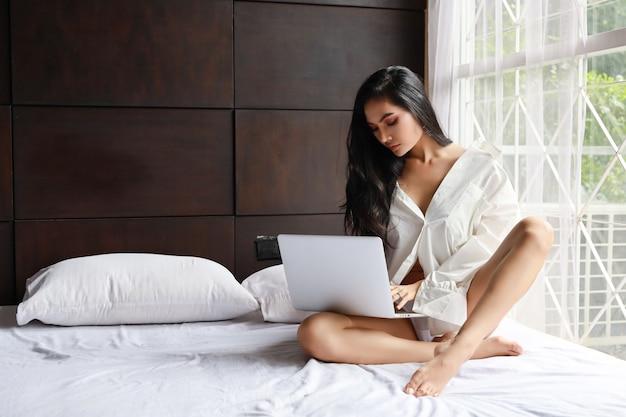 Платье взрослой внештатной азиатской сексуальной женщины нося белое работая на компьютере пока сидящ на кровати в спальне Premium Фотографии