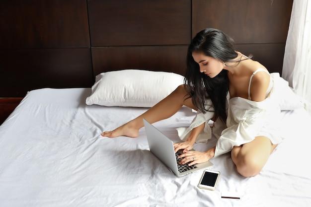 Взрослая внештатная азиатская женщина в белой рубашке работая на компьютере и сотовом телефоне в спальне с лицом красотки Premium Фотографии