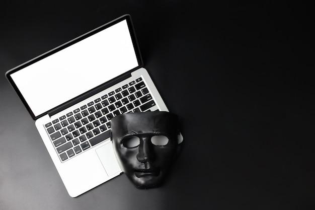 ハッカーとサイバー犯罪概念、黒い背景に白い画面を持つ新しいコンピューターに黒いマスク Premium写真