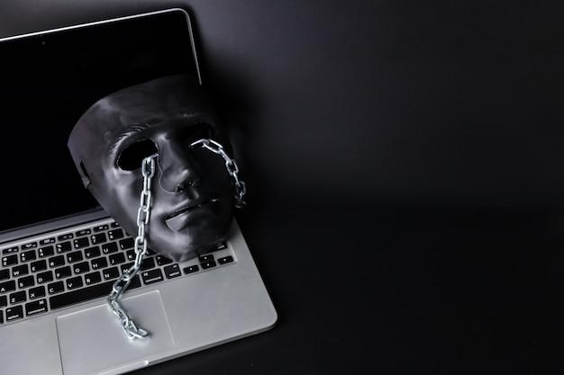 Концепция хакера и кибер-преступности, черная маска с цепью на новом компьютере на черном фоне Premium Фотографии