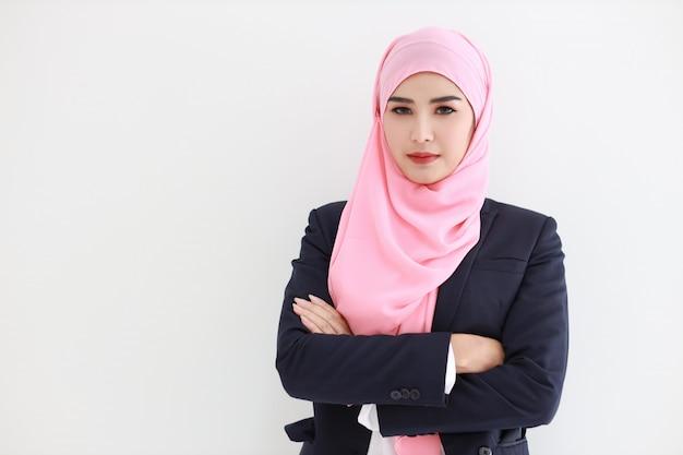 Довольно мусульманская молодая азиатская женщина нося голубой костюм усмехаясь уверенно Premium Фотографии