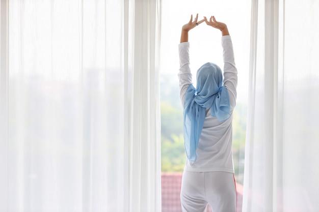 Вид сзади красивая азиатская мусульманская женщина носить белые пижамы, протягивая руки после вставать утром на рассвете. милая молодая женщина с голубой хиджаб стоя и расслабляющий глядя Premium Фотографии
