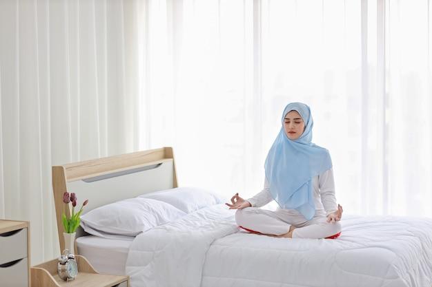 Молодая азиатская мусульманская женщина сидя на кровати и наслаждаясь раздумьем. красивая женщина в пижаме с голубым хиджабом практикует йогу в спальне с миром и спокойствием. концепция здорового образа жизни Premium Фотографии