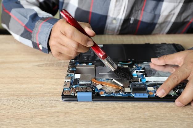 Техник человек, с помощью щетки для чистки ноутбука Premium Фотографии