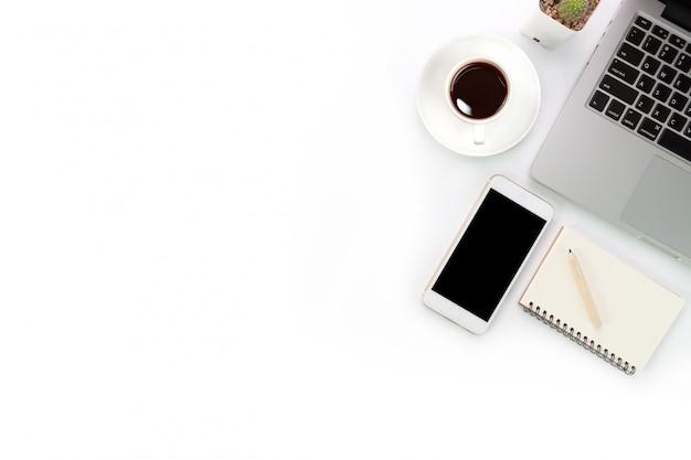 ラップトップコンピューターと携帯電話を持つ白いワークスペーステーブル Premium写真