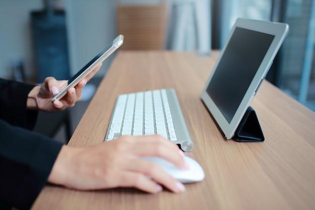 テーブルと携帯電話を使用して実業家の手 Premium写真