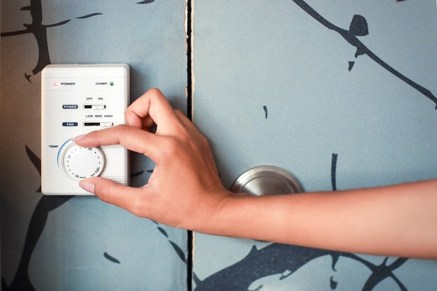 Женская рука с помощью термостата Premium Фотографии