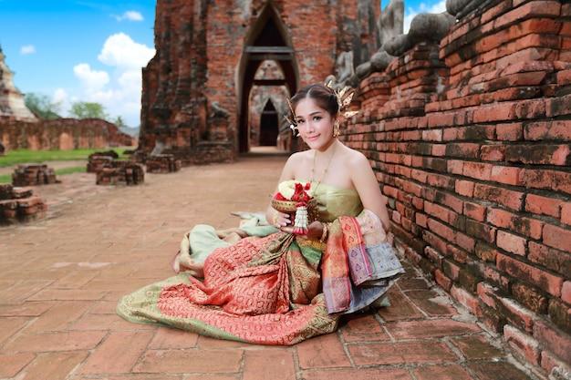 手にステアリングホイールの花を持つ古代寺院のタイの伝統的な衣装でアジアの女の子をファッションします。 Premium写真