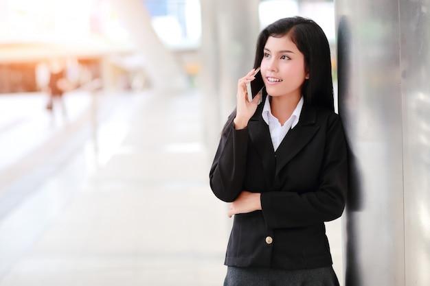 Коммерсантка используя мобильный телефон Premium Фотографии