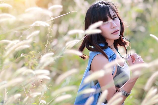 幸せで楽しい時間を過ごし、自然の中で不愉快なアモウングラスフィールドを持つ若くてかわいい女の子 Premium写真