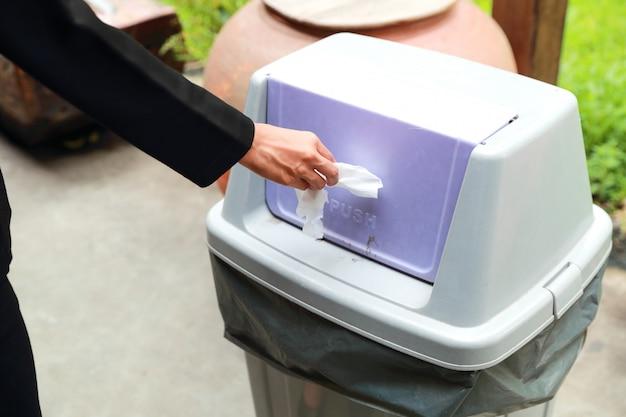 ゴミ箱に紙を投げるクローズアップ女性手 Premium写真
