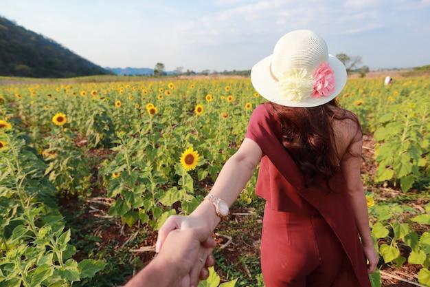 自然のひまわり畑の中で手をつないでカップル Premium写真