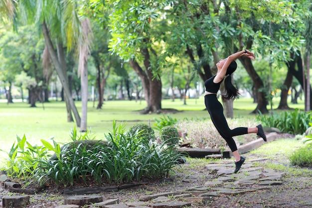 健康的でスポーティな若い女性は屋外ヨガストレッチ Premium写真
