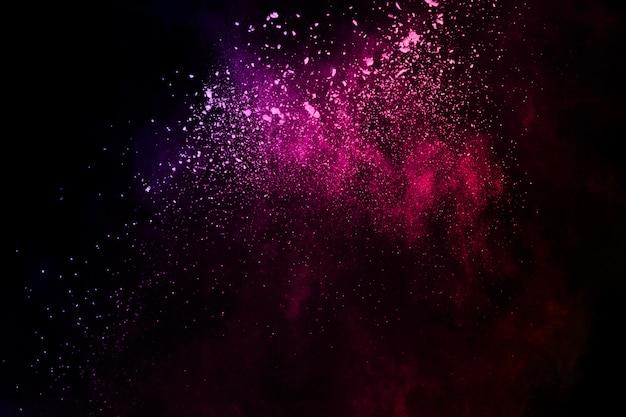 黒の背景に抽象的な色塵爆発。 Premium写真