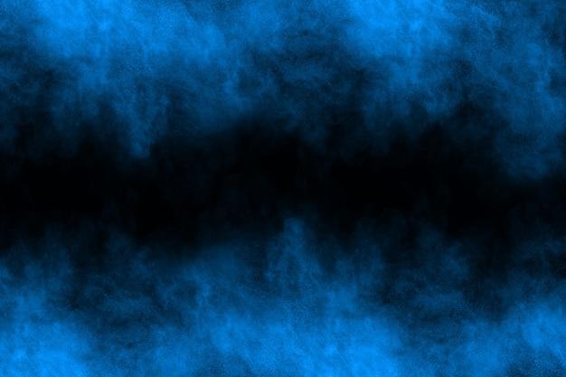 黒い背景に青い粉の爆発。 Premium写真