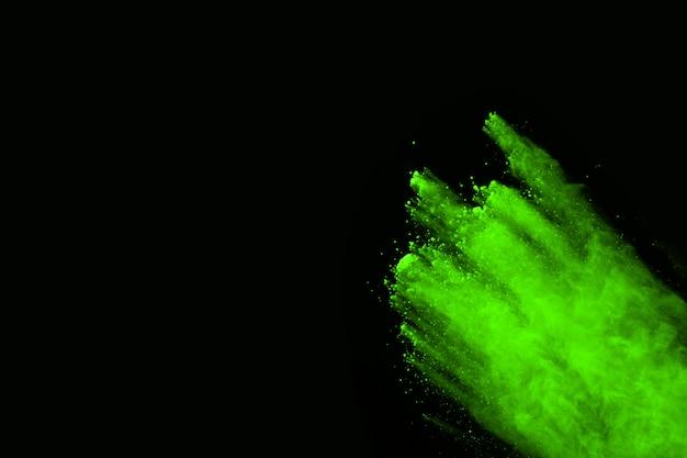 Движение абстрактного взрыва пыли замерзшего зеленого на черном фоне. Premium Фотографии