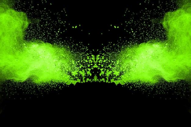 Остановить движение порошкообразного зеленого на черном фоне. взрывоопасный зеленый порошок на черном фоне. Premium Фотографии