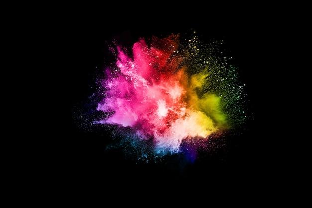Абстрактный цветной взрыв пыли на черном. Premium Фотографии