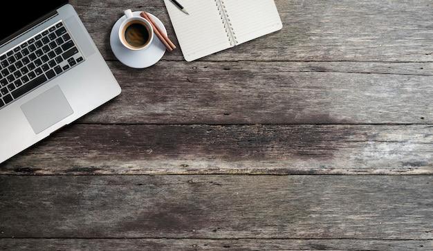 一杯のコーヒーと古い木製のテーブルに日記の空白のページのモックアップラップトップコンピューター。 Premium写真