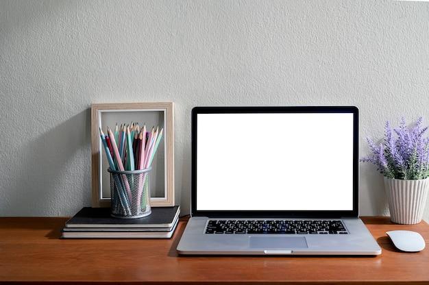 空白の画面と木製のテーブルの供給のモックアップノートパソコン。 Premium写真