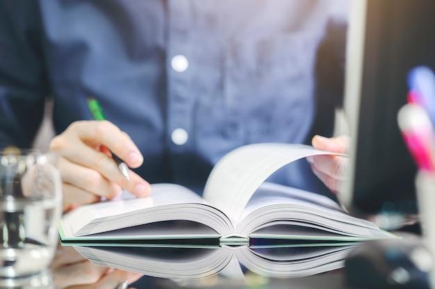 オフィスのテーブルに座って本を開いて読むクローズアップ男。 Premium写真